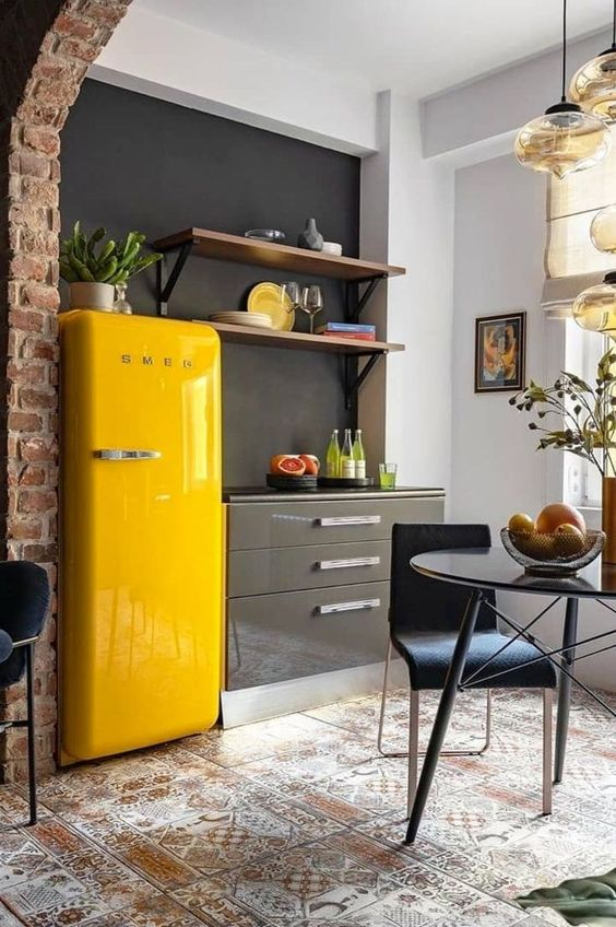 a sleek grey kitchen with a chalkboard wall, open shelves, a sunny yellow fridge and a dining zone with pendant lamps