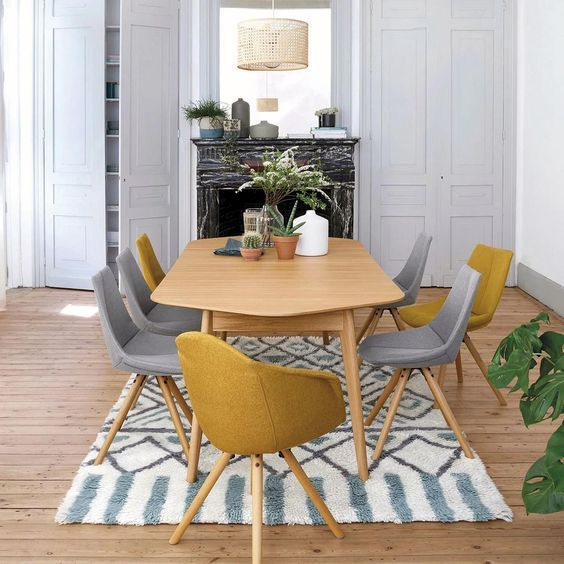 a small and cozy modern dining space with grey storage units, a black marble fireplace, a wooden chair, grey and yellow chairs and potted plants
