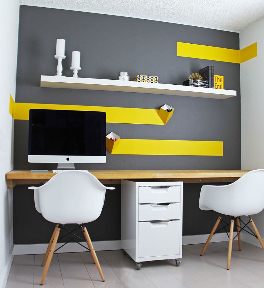 a small contemporary home office with a grey accent wall with bold yellow touches and an open shelf, a shared desk and a couple of chairs