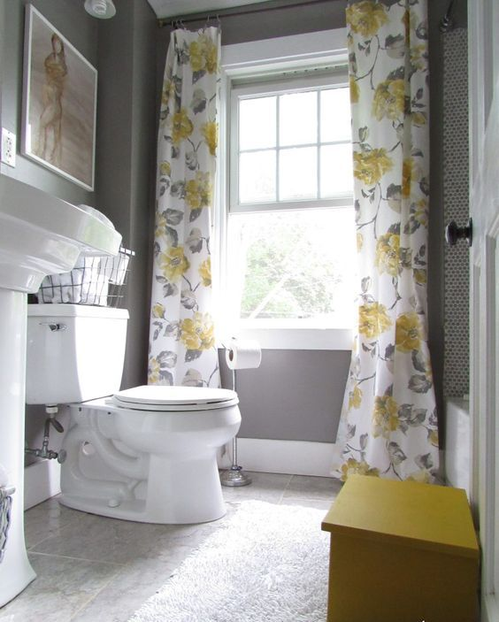 a small vintage bathroom with grey walls and a floor, grey and yellow floral curtains, white appliances is a very chic space