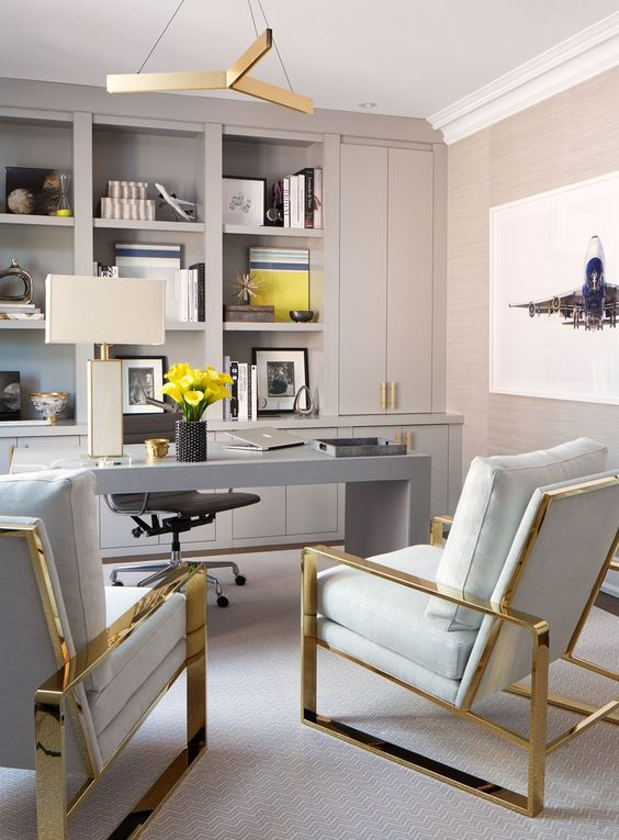 a sophisticated home office in dove grey, with built in storage units, a sleek grey desk and gold and grey chairs plus yellow touches
