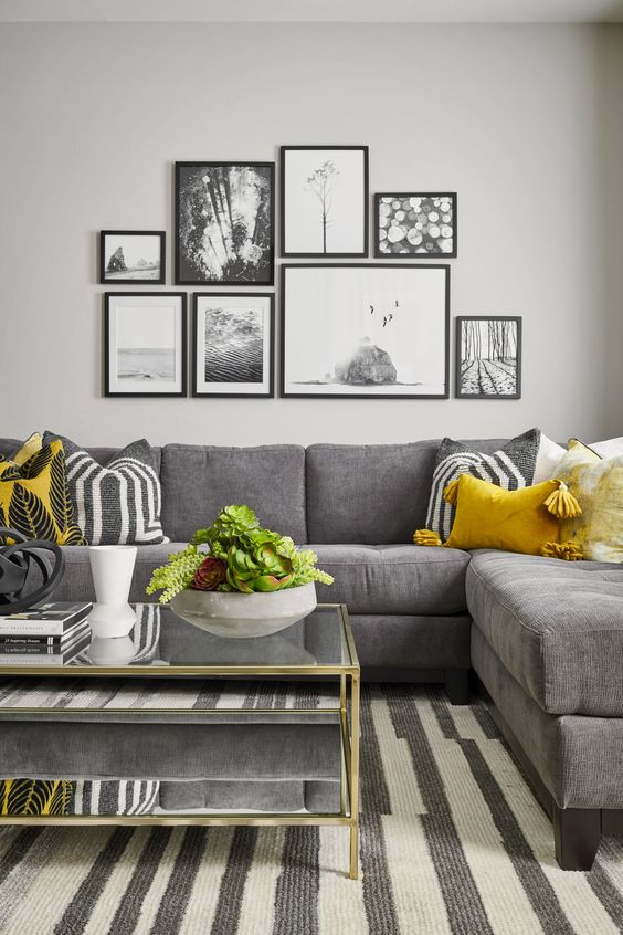 a stylish living room with a grey corner sofa, a striped rug, a tiered coffee table, a black and white gallery wall and some yellow pillows