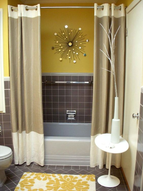 a stylish mid-century modern bathroom with yellow and grey walls, a sunburst decoration, color block curtains