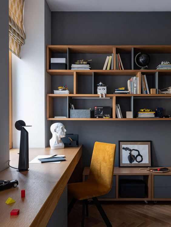a stylish modern home office with graphite grey walls, a windowsill desk, an open shelving unit, a yellow suede chair and a cabinet