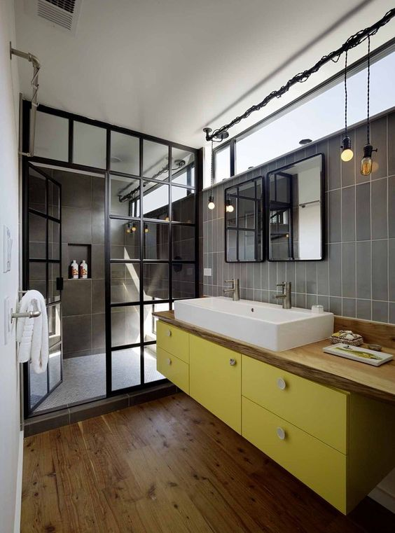 a super chic bathroom with grey tiles, a floating yellow vanity, a wooden countertop, a shower space with a framed glass space divider