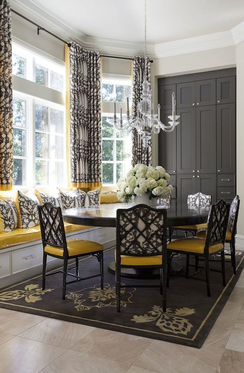 a vintage and refined dining room with a bay window, a windowsill seat, a round table, black and yellow chairs, a graphite grey storage unit