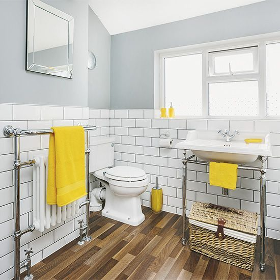 a vintage bathroom with grey walls and white subway tiles, vintage fixtures, mirrors and yellow accessories and touches