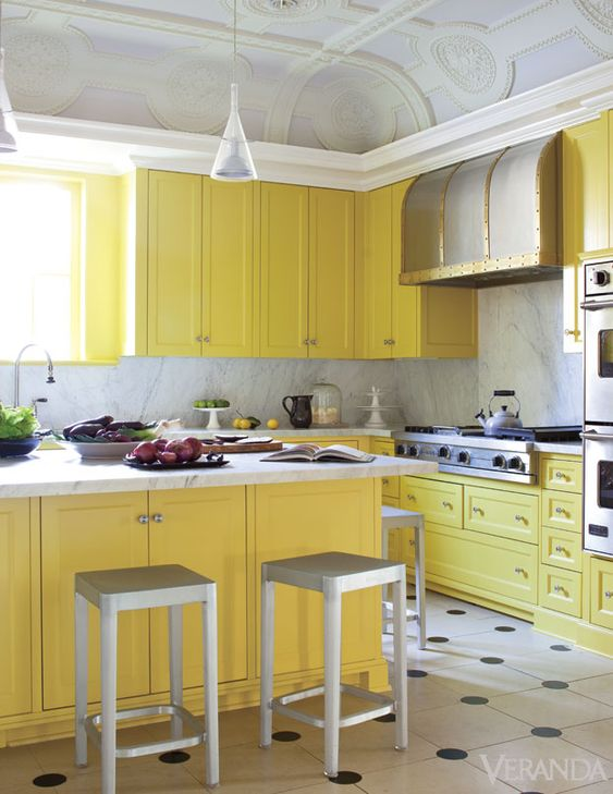 a vintage yellow kitchen with a grey marble backsplash and countertops, metal stools, a vintage metal hood