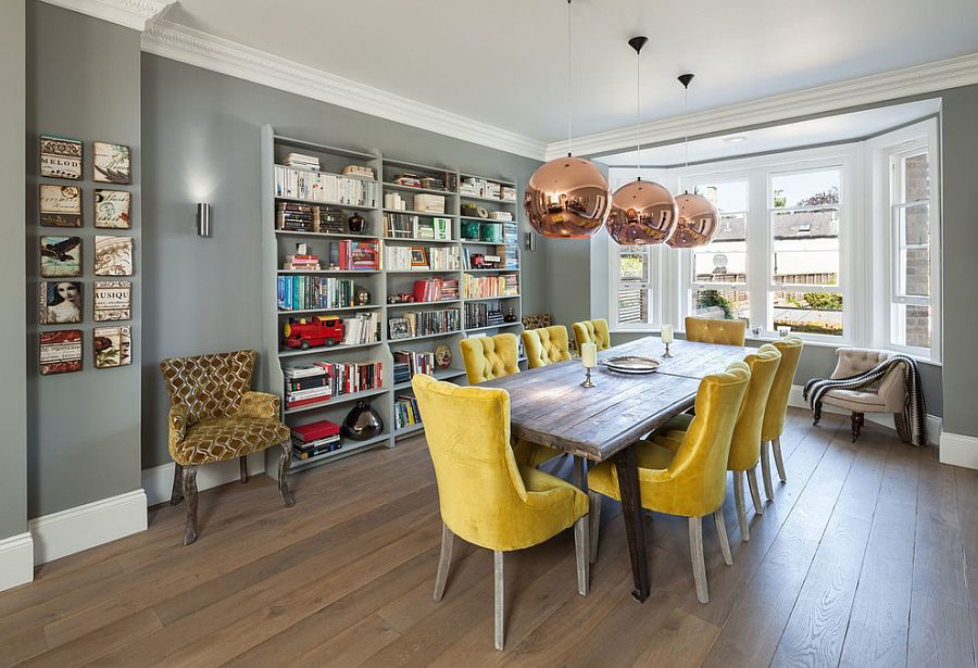 a welcoming dining room with a bay window, grey walls, a wooden table, yellow chairs, copper pendant lamps and a wall storage unit