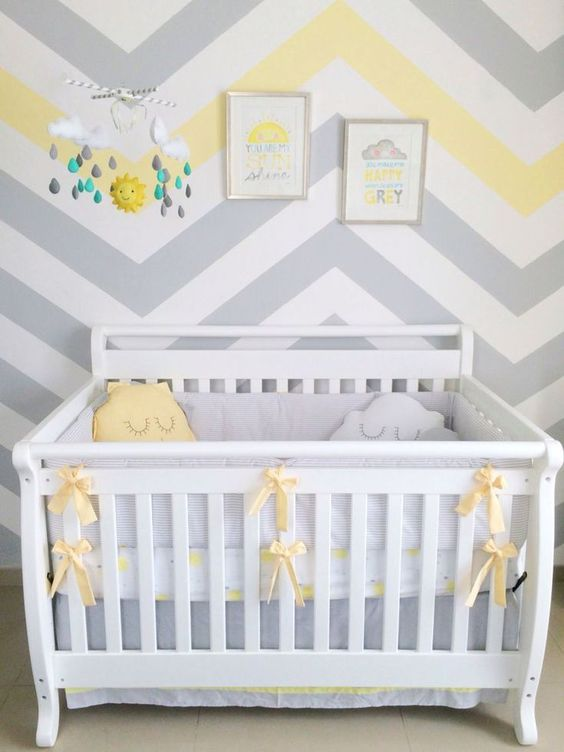 a welcoming nursery with a chevron accent wall, a white crib with grey and yellow bedding, a bright mobile and artworks