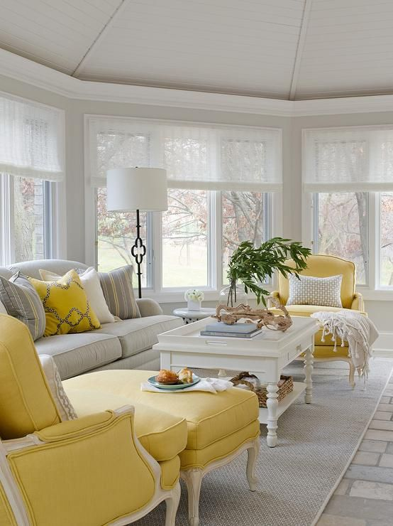 a welcoming vintage living room with yellow and neutral furniture, printed pillows, greenery, a floor lamp and a bay window
