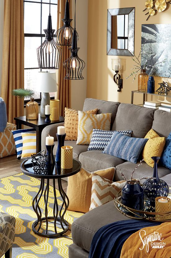 a whimsical living room with yellow walls, grye furniture, blue and yellow pillows and blankets, pendant lamps and a coffee table plus touches of navy