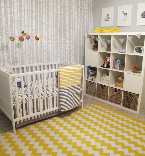 a woodland nursery with woodeland wallpaper, white furniture, a bright chevron rug, printed bedding and a cute gallery wall