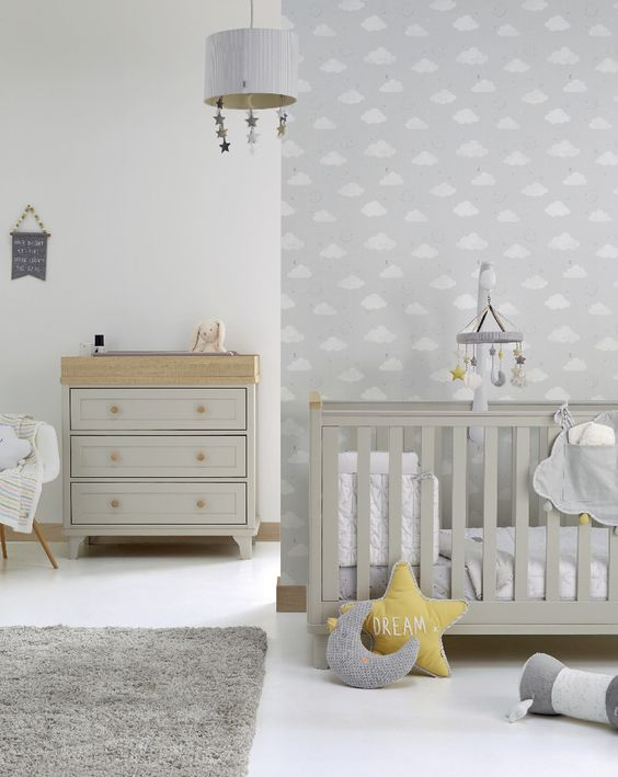an airy grey and white nursery with a grey crib and dresser, mustard and grey pillows, mobiles and a cozy rug