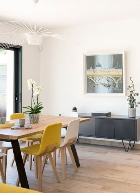 an airy modern dining room with a grey storage unit, a dining table, yellow and white chairs and a pretty retro chandelier