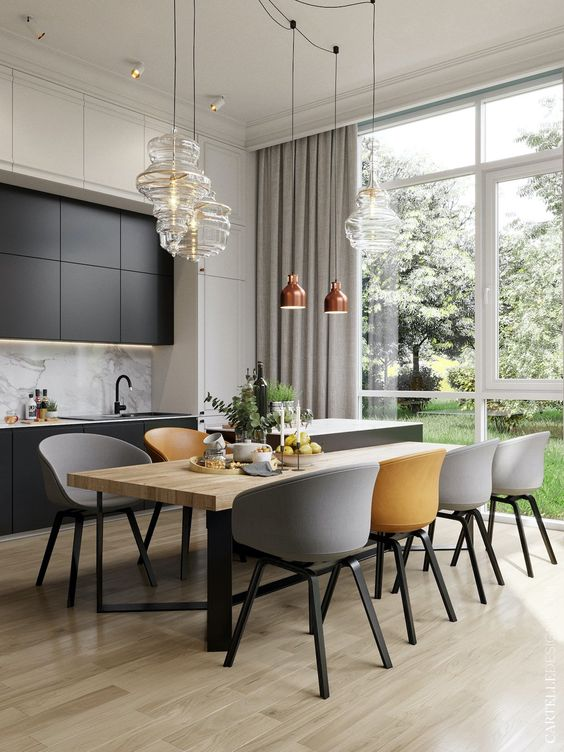 an elegant dining zone with a wooden table, grey and yellow chairs, glass and copper pendant lamps is very chic