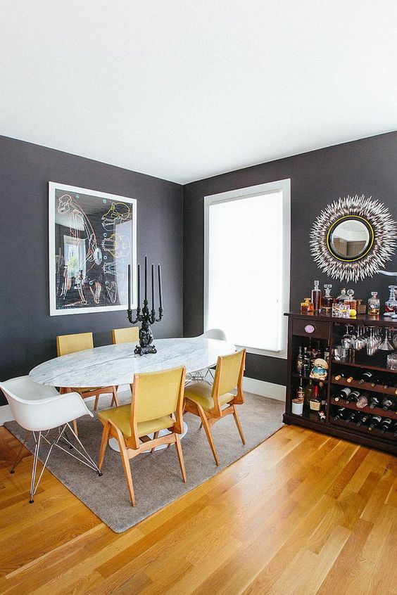 an elegant grey and yellow dining room with graphite grey walls, an oval marble table, yellow chairs, a dark home bar and a sunburst mirror