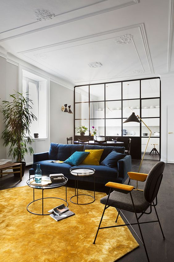 an elegant living room with a navy sofa, a black and yellow chair, a yellow rug and pillows plus potted plants