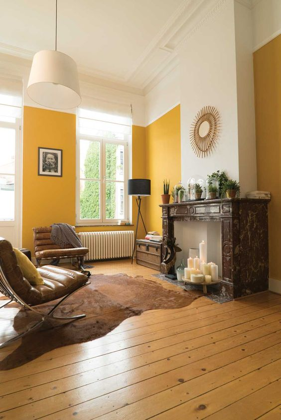 an elegant living room with yellow walls, a fireplace with candles, leather chairs and potted plants on the mantel