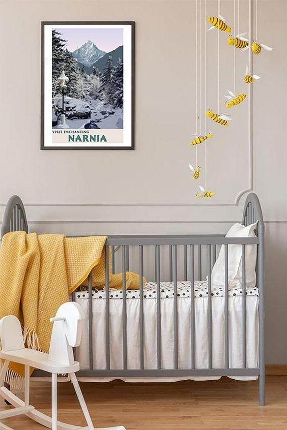 an ethereal nursery with dove grey paneled walls, a vintage grey crib, a bee mobile and some yellow textiles
