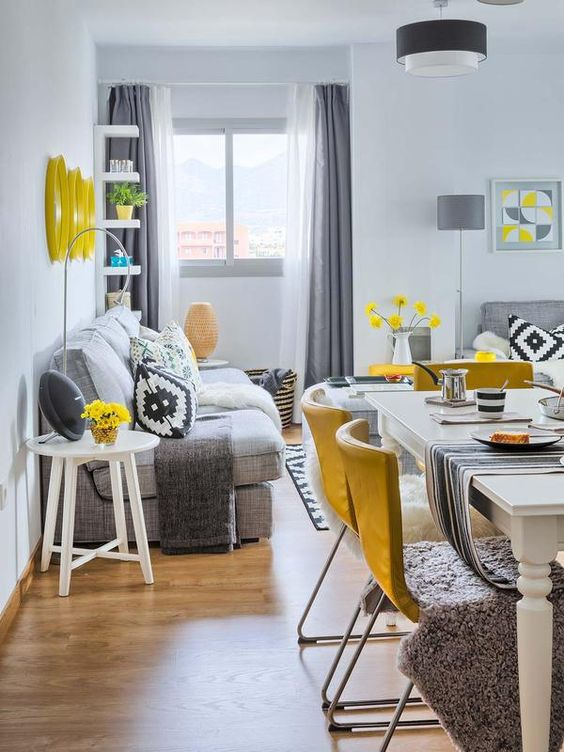 an open layout with a dining and a living room, done in grey, white and accented with sunny yellow is a cool and bold idea