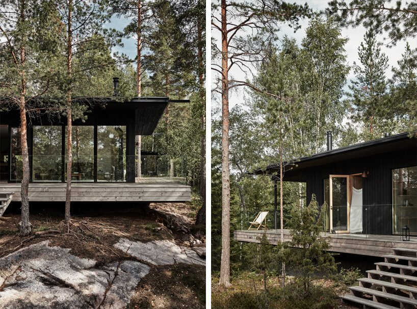 The cabin is black, there's a wooden deck around the house and a terrace