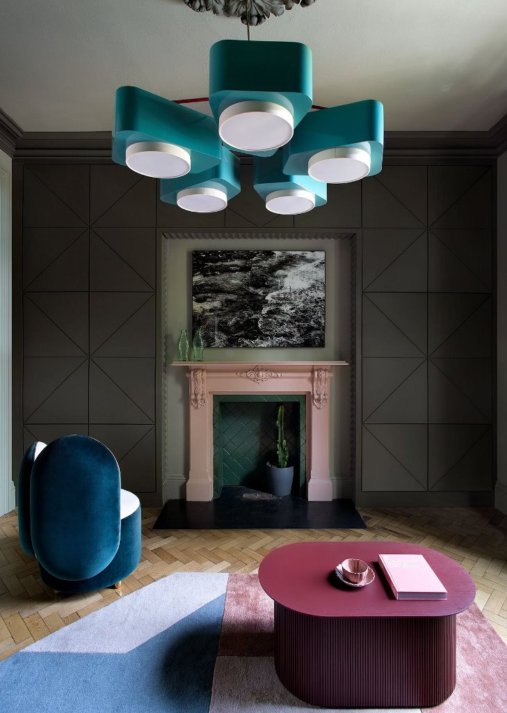 The living room features a green and pink fireplace, a blue chandelier, a navy chair and a burgundy table