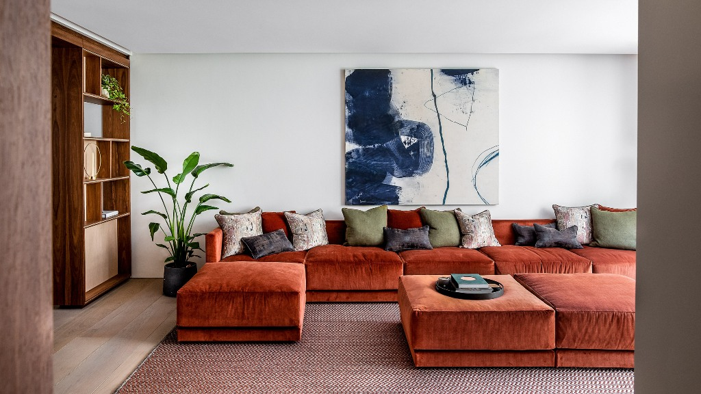 The living room shows off a fantastic rust-colored sectional, a storage unit, a blue artwork and some muted pillows