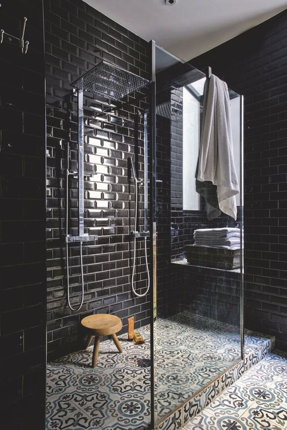 a chic black bathroom with glossy tiles and patterned ones on the floor, a glass shower space is refined