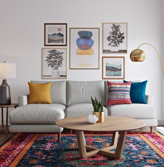 a colorful global style living room with a bold rug, a gallery wall with bright artworks and colorful pillows