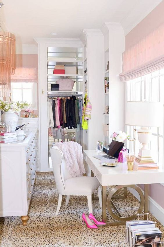 a glam girlish closet that doubles as a home office, decorated with leopard, pink touches and some brass is chic