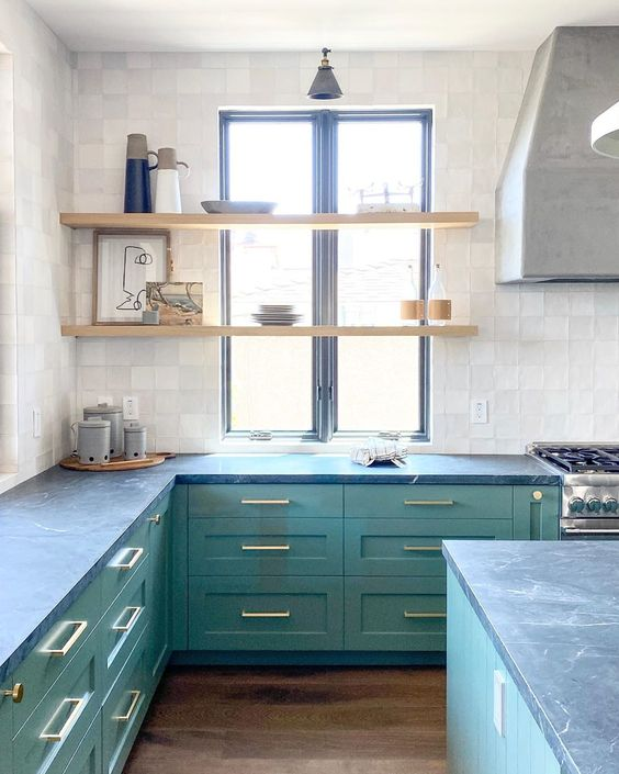 a non typical shade of green plus grey stone countertops make the kitchen look unusual and very bold