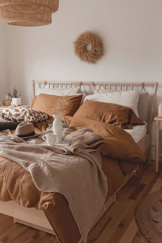 an earthy bedroom in boho style, with wooden furniture, terracotta bedding, a wicker lamp and a wreath of wheat