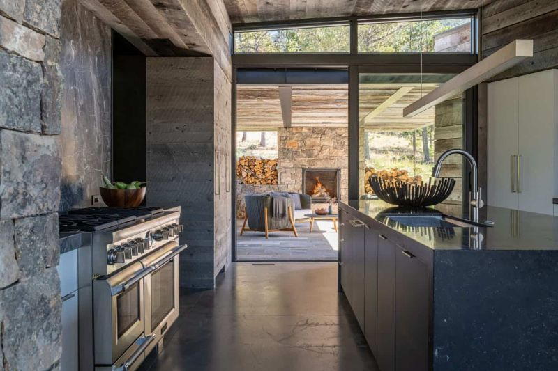 The kitchen features rustic wooden cabinetry, a dark kitchen island and a stone backsplash, there's an access to a covered patio