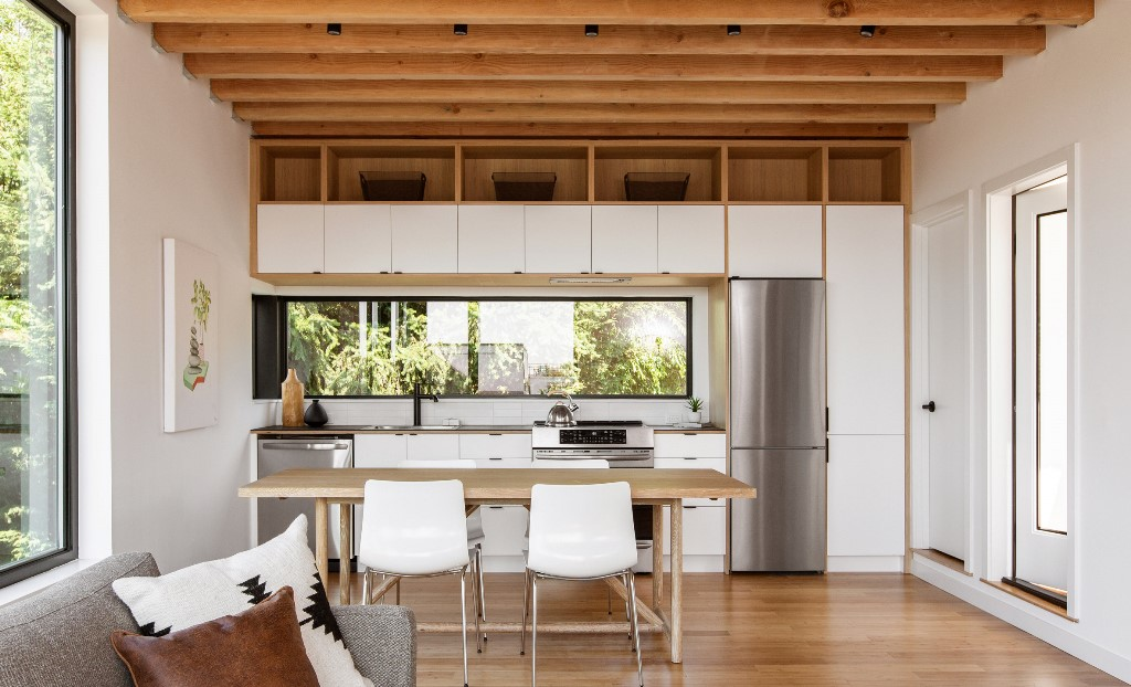 The open layout shows a kitchen, dining space and living room, there's much natural light and an airy feeling