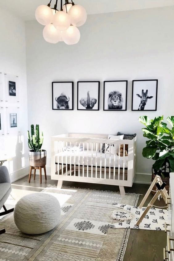 a chic gender neutral nursery in simple colors and with boho touches, potted plants and a black and white gallery wall