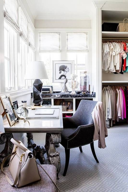 a stylish light filled cloffice with elegant heavy furniture, with contrasting neutral and dark touches and with cool clothes