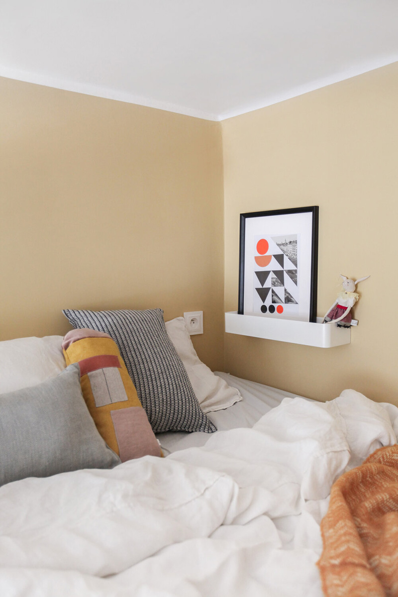 A socket and a ledge with an artwork make the sleeping space practical and functional