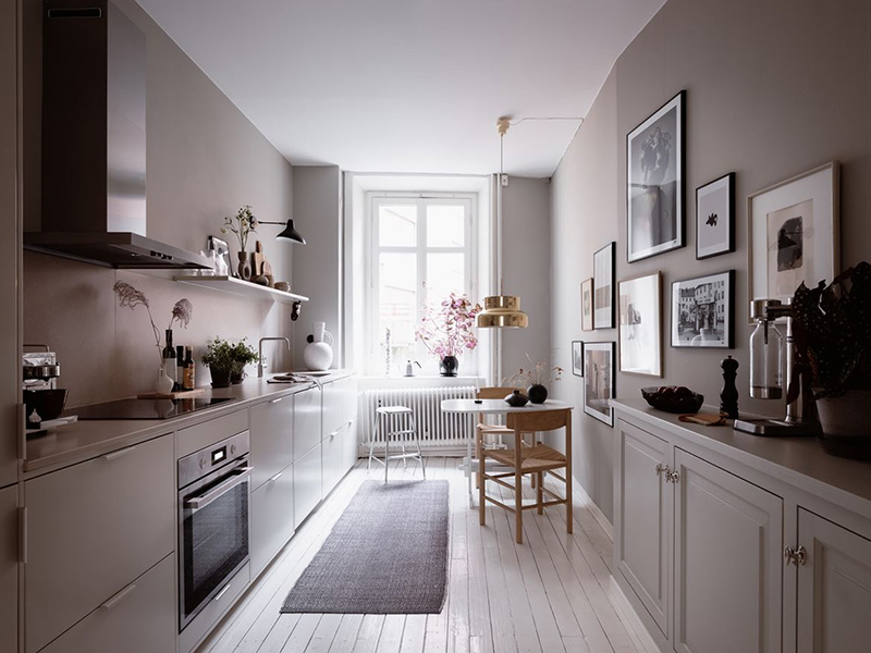 The kitchen is done with modern and vintage grey cabinetry, with a mauve backsplash and a large gallery wall