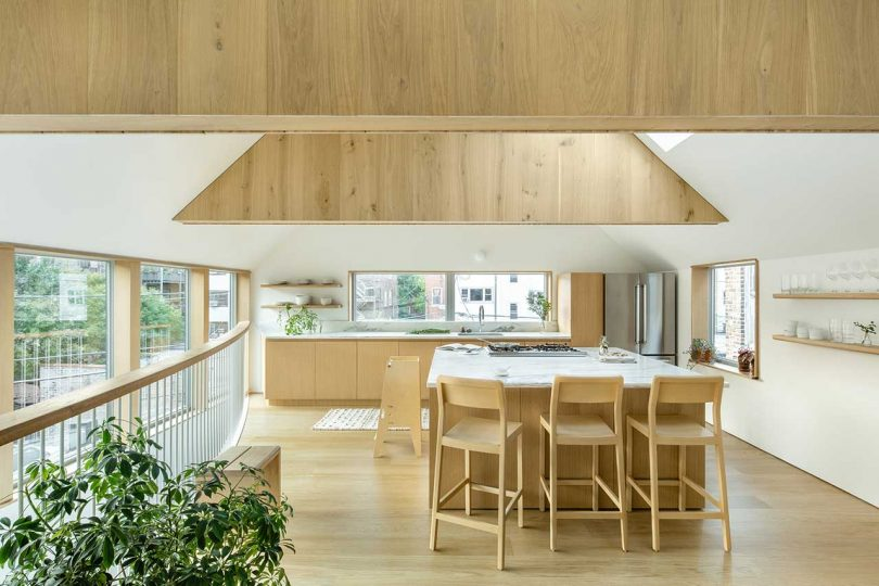 The kitchen is minimal, with light-stained cabinets with white stone countertops and a kitchen island with a breakfast zone