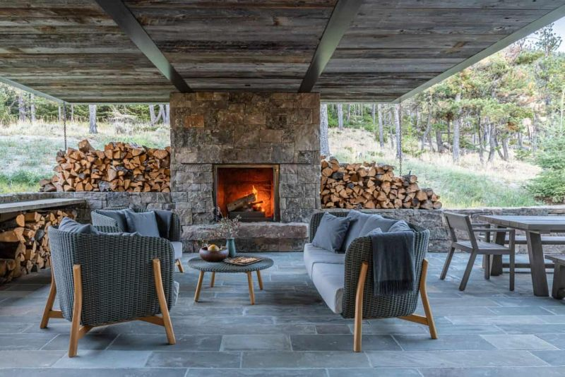 The patio shows off a stone clad fireplace, some wicker furniture, lots of firewood
