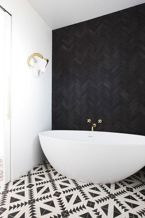 a jaw-dropping bathroom with a black herringbone tile wall, geometric printed tiles and a cool oval bathtub
