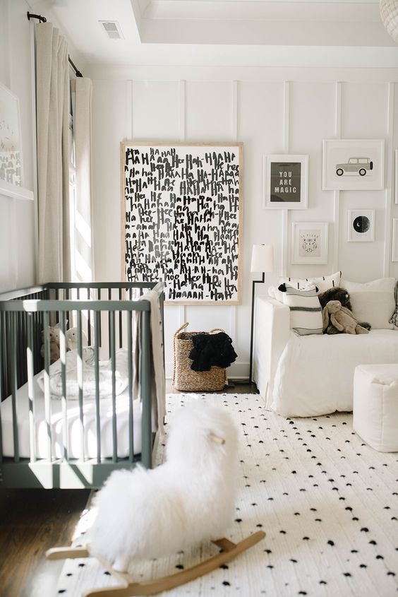 a stylish monochromatic nursery with graphit artworks, a green crib, printed textiles is welcoming