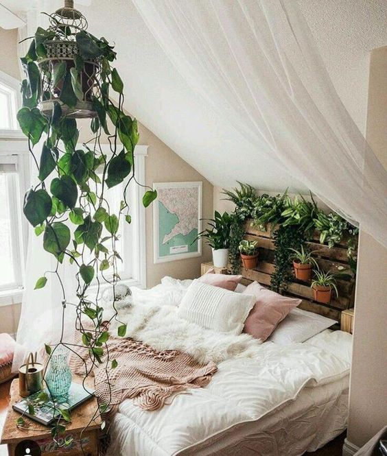 an attic boho bedroom with a pallet headboard garden and a suspended cage with greenery is gorgeous