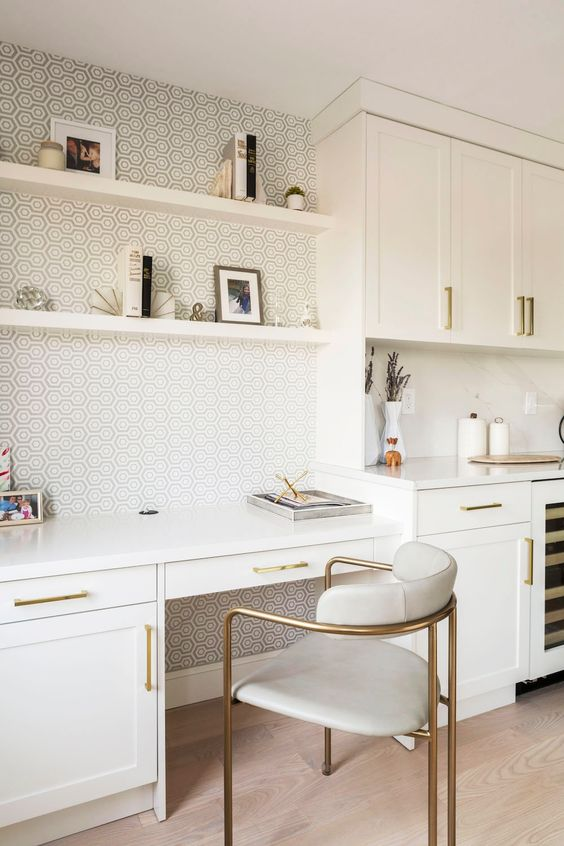 an elegant and refined white kitchen with a home office, with brass touches and a stylish wallpaper wall