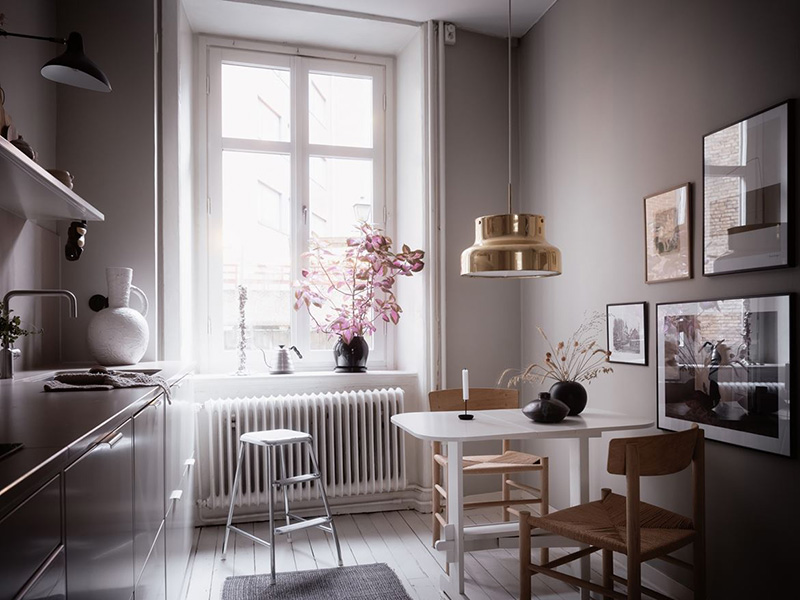 A tiny breakfast space is located by the window and accented with a gold pendant lamp