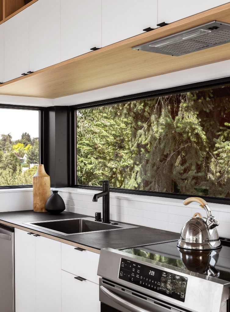 The kitchen is done in white, with black countertops and windows as backsplashes
