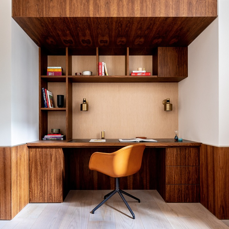 There's a working space built into a corner, with a desk, a storage unit and a ceiling