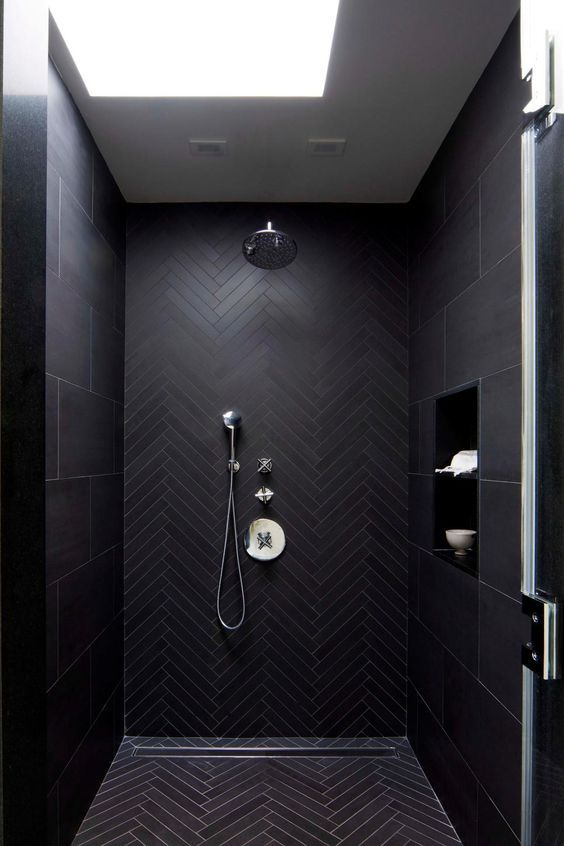 a contemporary moody black bathroom with herringbone and large scale tiles and a skylight to refresh the space