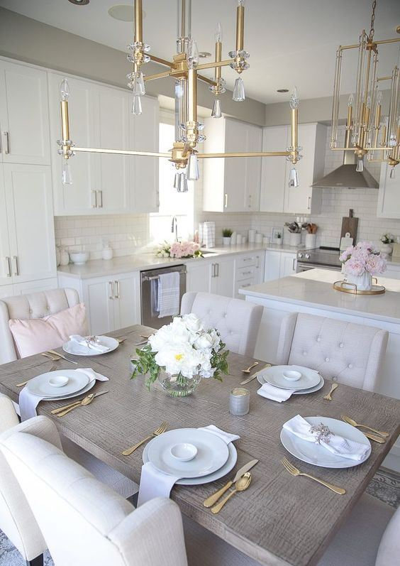 a neutral and very elegant eat-in kitchen with stylish cabinetry, gold and crystal chandeliers and neutral furniture